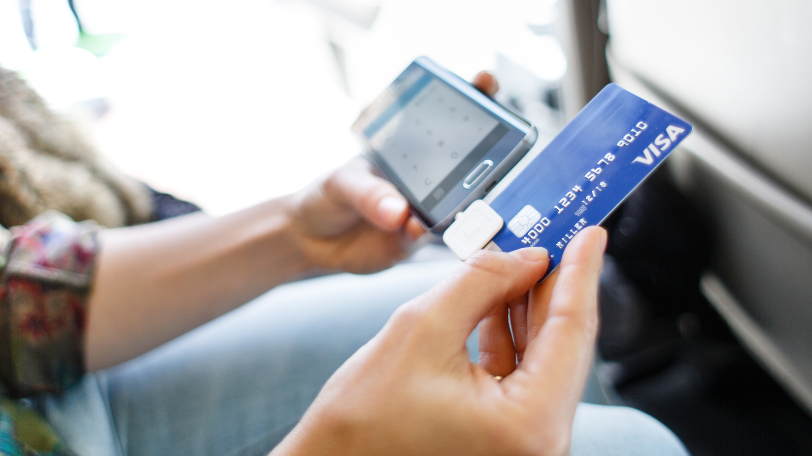 A woman swiping a card in a mobile card reader.