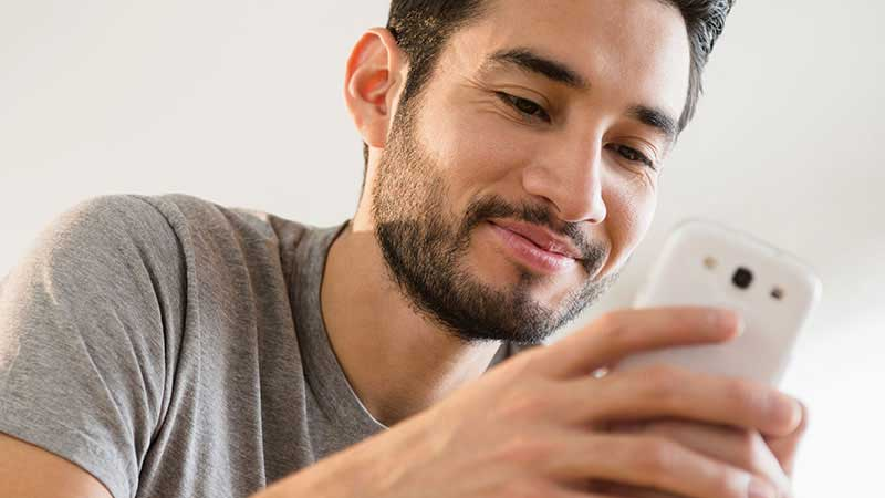 A bearded young man looks at his phone.