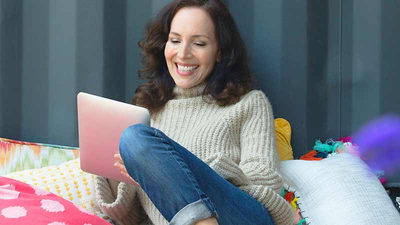 A smiling woman uses her tablet to shop online.
