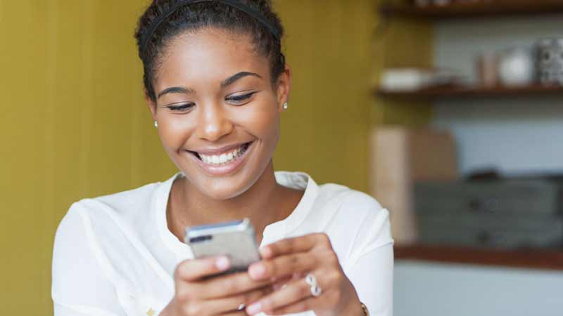 A smiling woman looks at her phone.